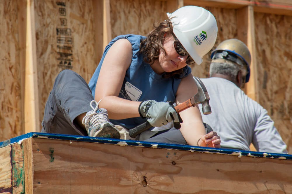 Woman working on a building with her Habitat for Humanity hat on