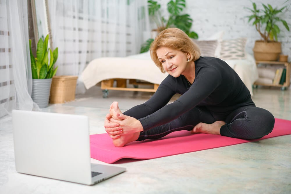 Woman stretched over her yoga mat, looking at her computer