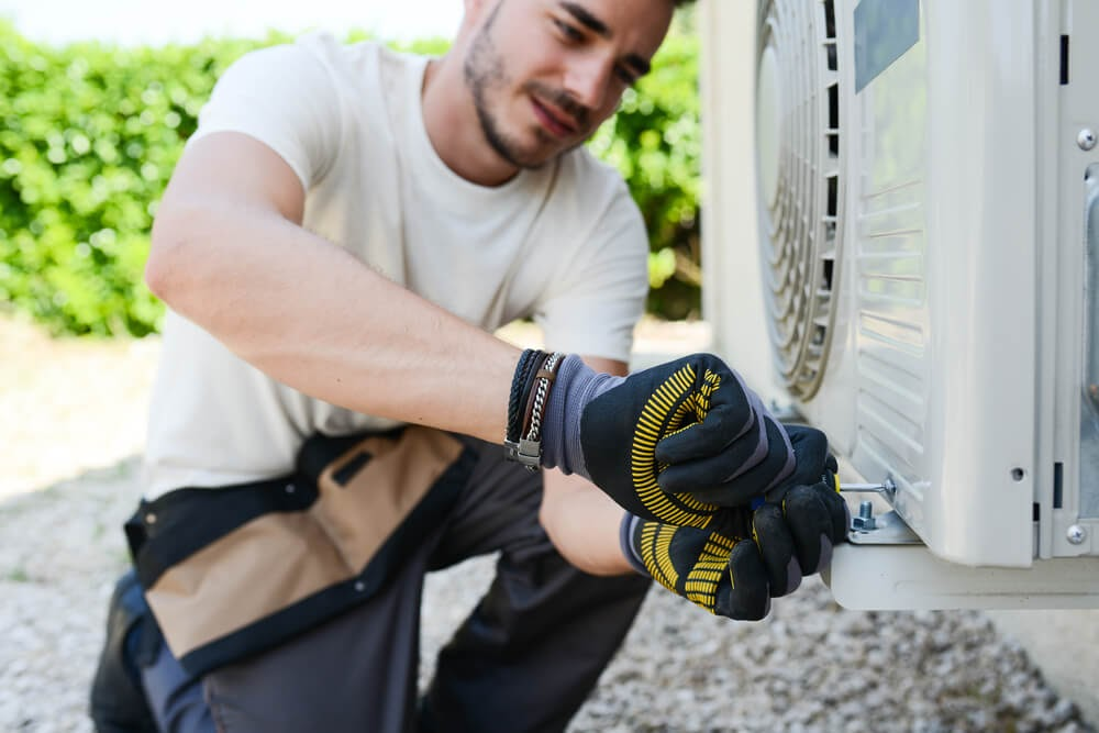 Man with gloves tightening a screw on an a/c unit cover