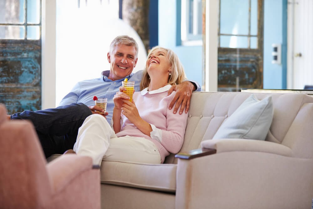 Couple enjoying retirement, cuddled on their couch
