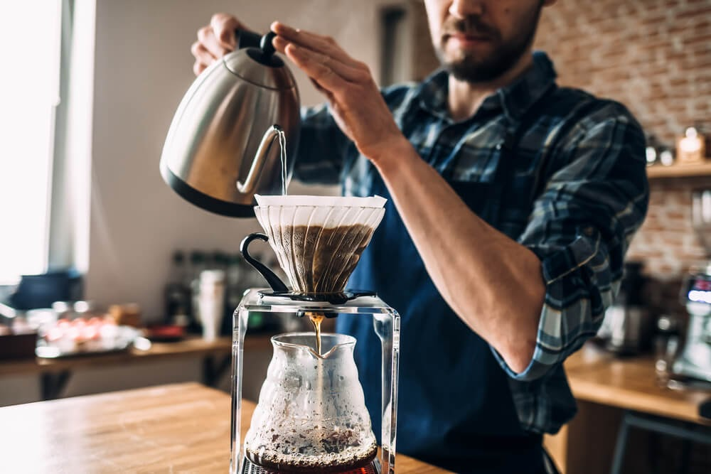 Man brewing pour over mushroom coffee.
