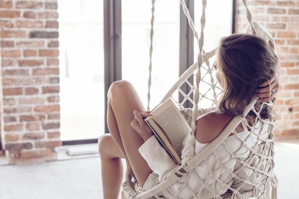 Woman sitting in chair hammock enjoying a  good book