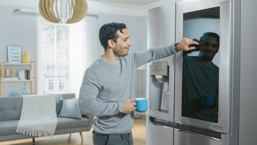 Man cleaning his smart fridge