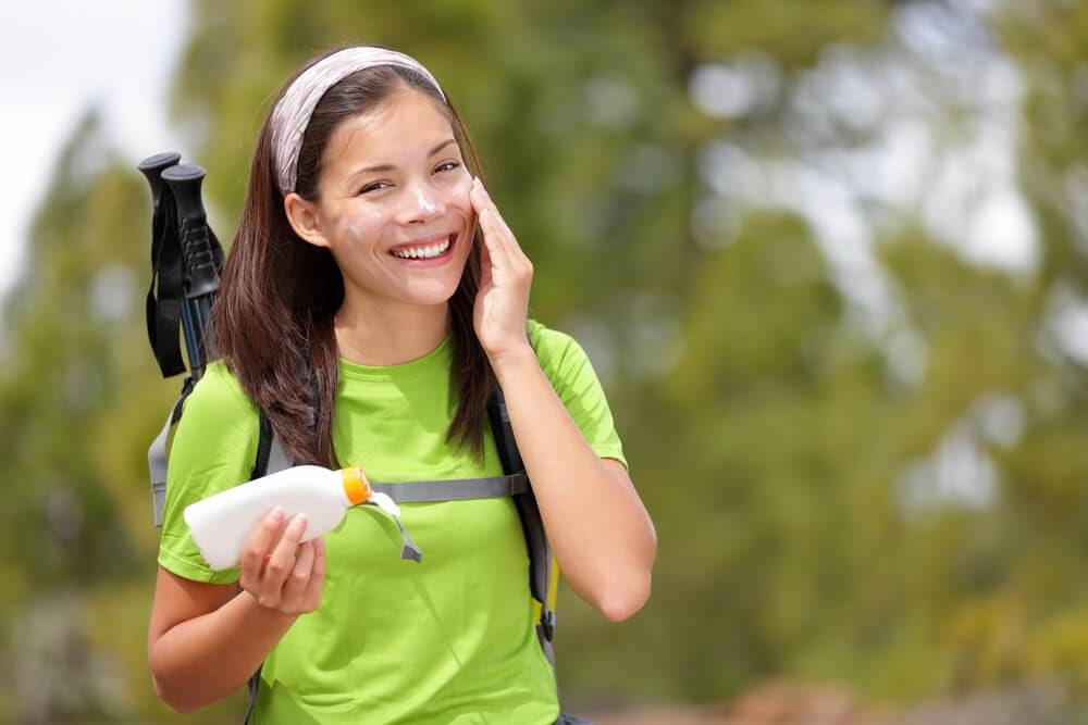 Woman happily putting sunscreen on her face while hiking