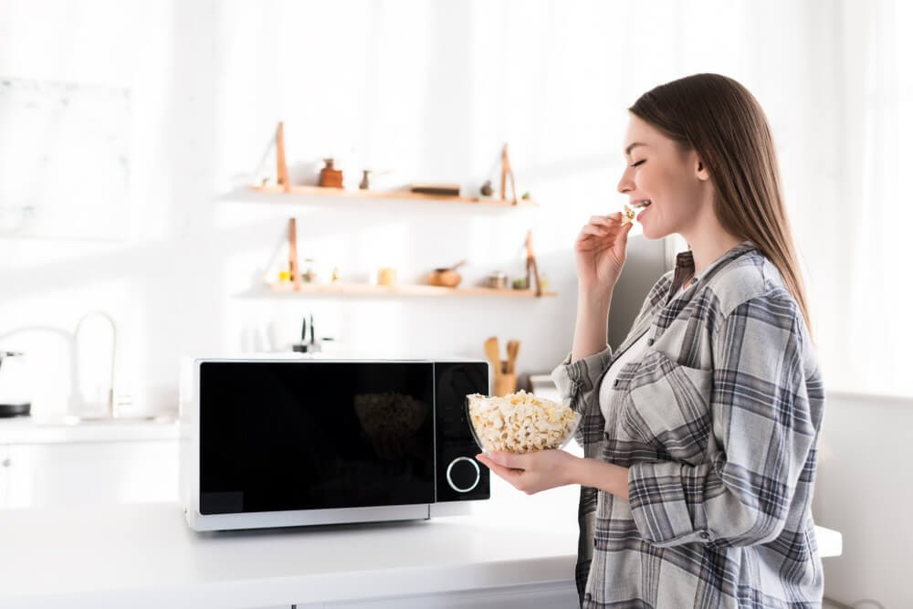 Woman enjoying popcorn from her freshly cleaned microwave