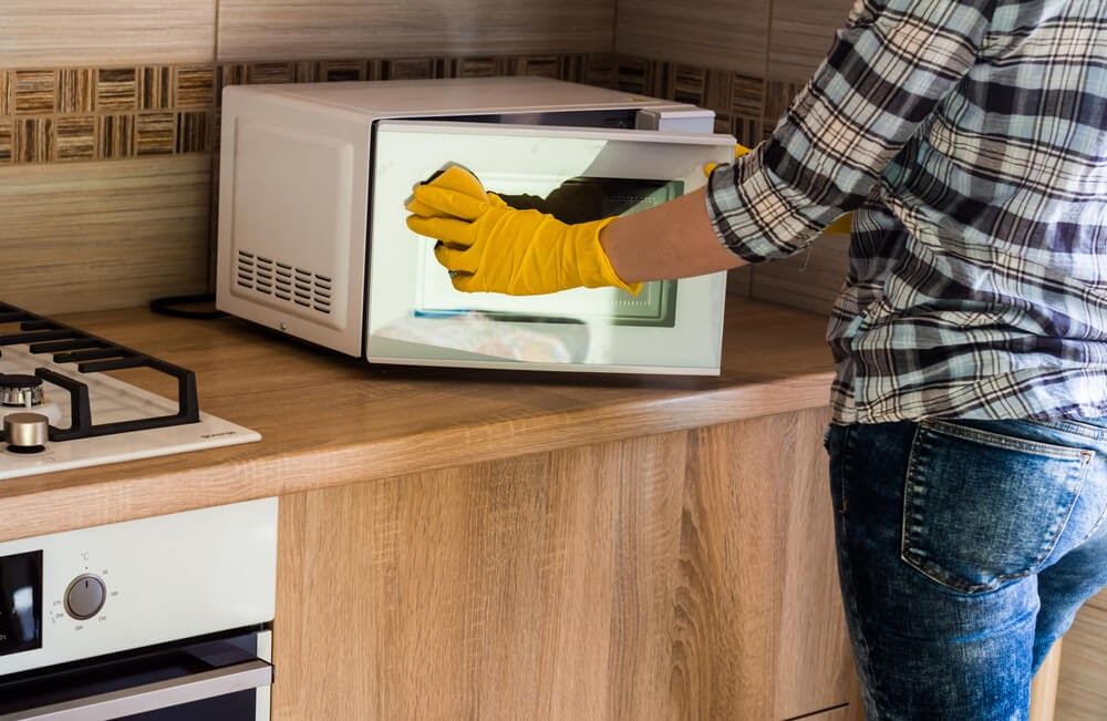 Person in a blue plaid shirt and jeans scrubbing their microwave in yellow latex glovese