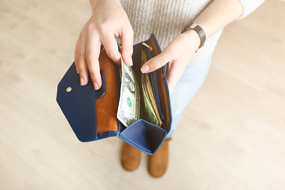 Woman pulling cash out of her wallet