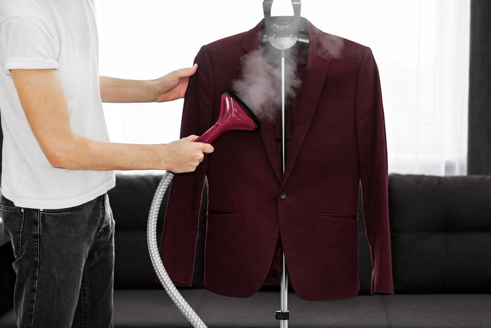 Man steam cleaning a rad maroon suit
