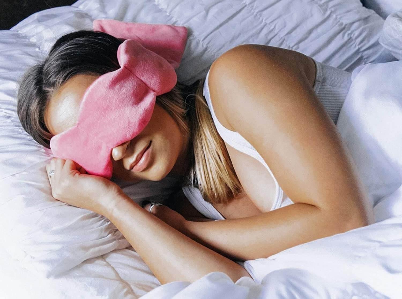 Woman sleeping soundly with her pink, fuzzy sleepmask