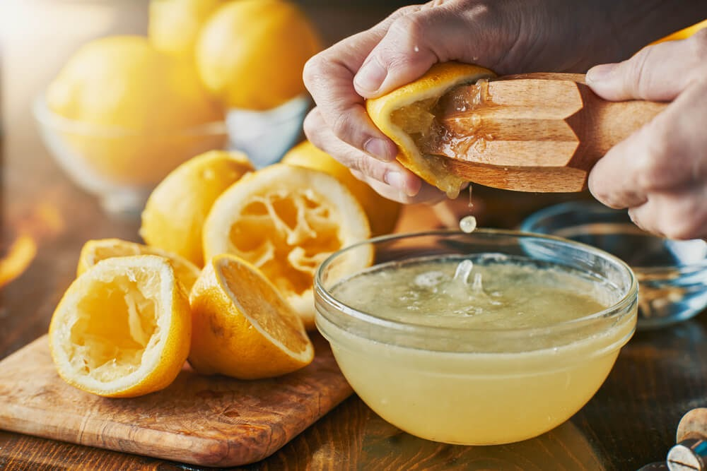 Juicing lemons into bowl in a sun-filled room.