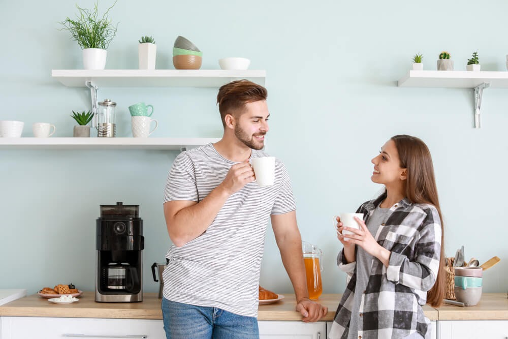 Young couple drinking coffee in light blue kitchen.