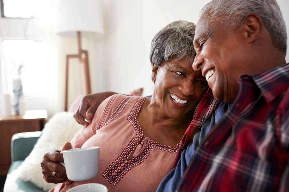 Older couple drinking coffee in living room and laughing.
