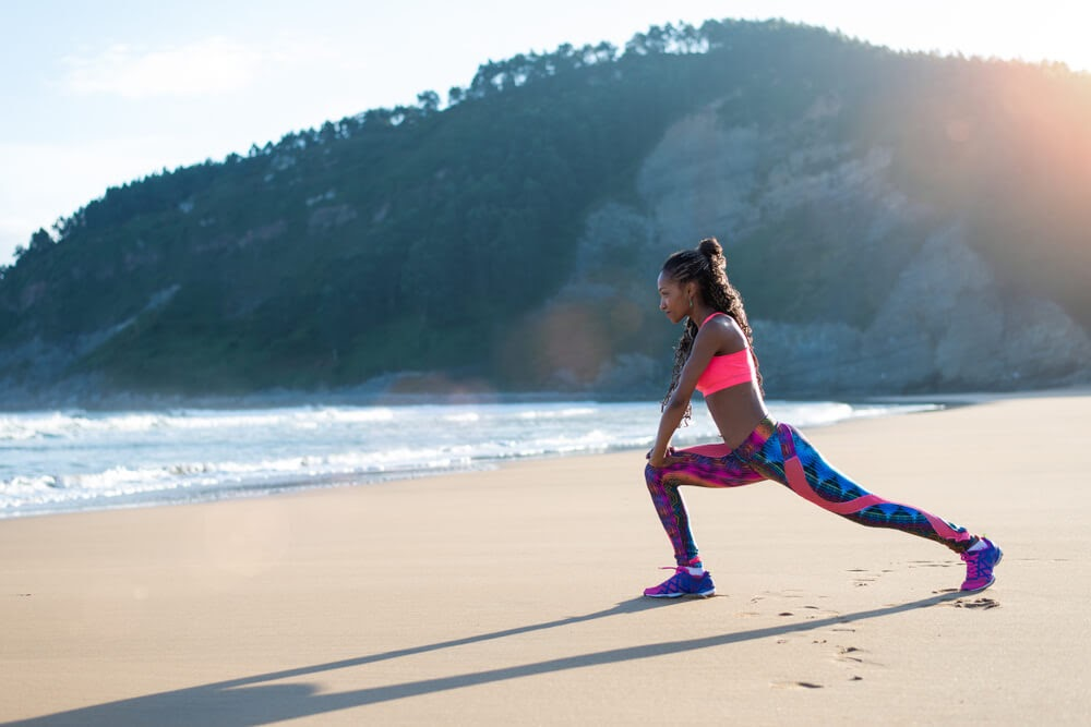 Woman looking fierce while lunging on a beach