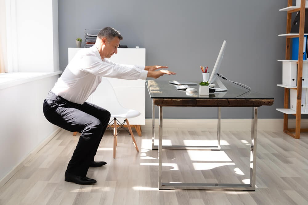 Man doing squats in front of his home desk