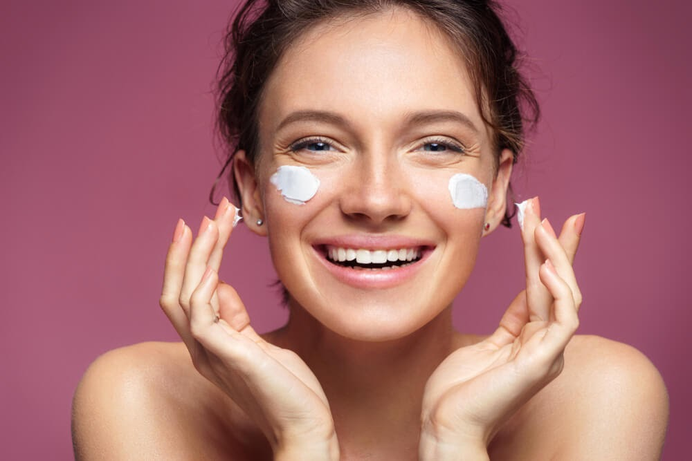 Woman smiling while applying cream to her cheeks
