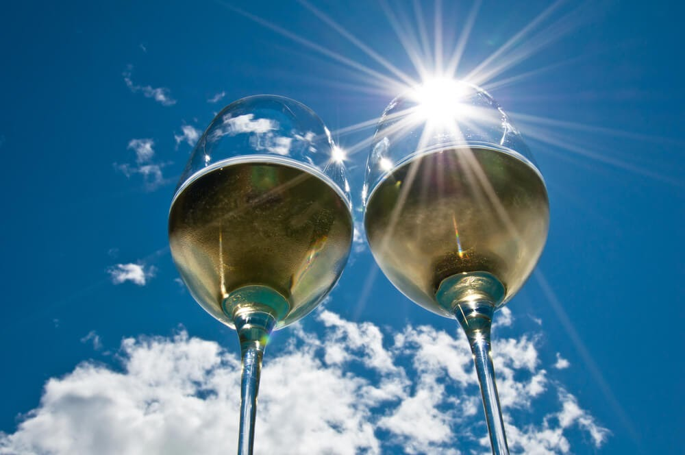 Two glasses of white wine glowing in the sun