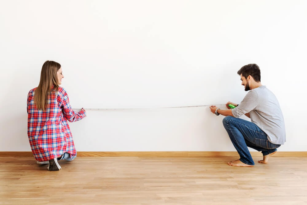 Couple measuring their potential couch against the living room wall