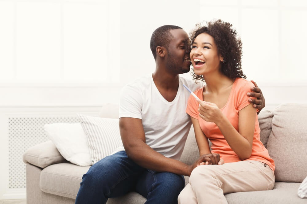 Man and woman canoodling on the couch with a pregnancy test