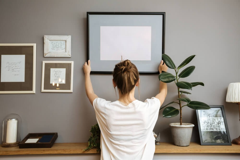 Woman hanging up picture