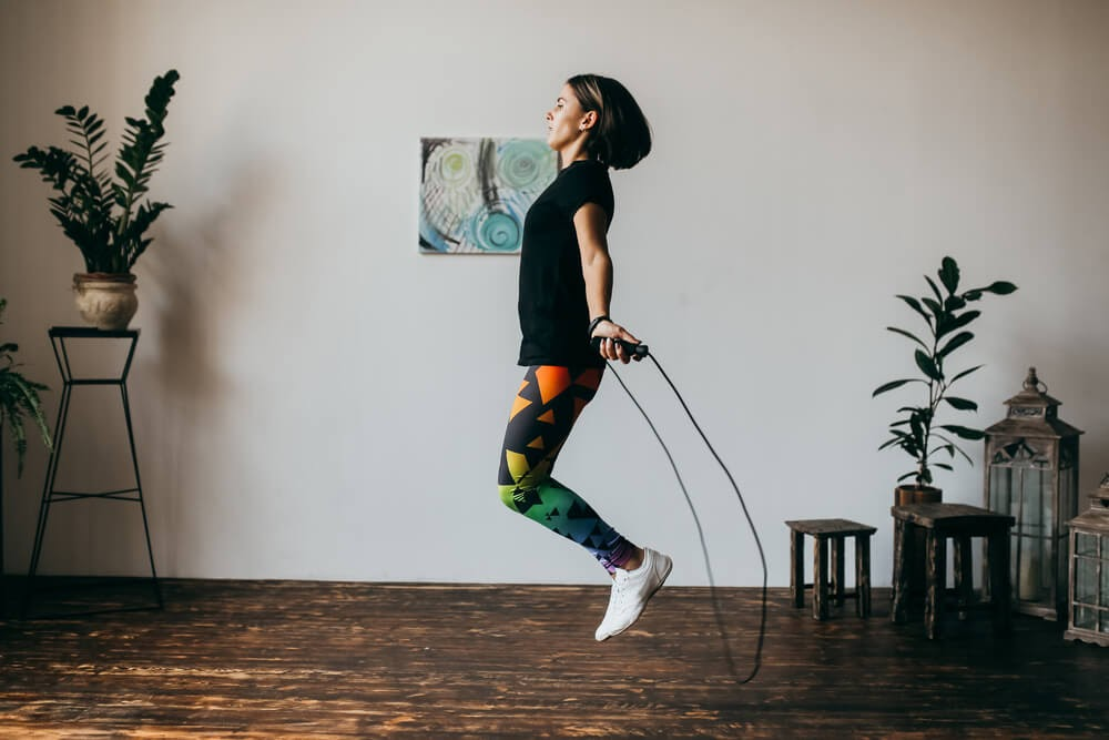 Woman jump roping in her living room