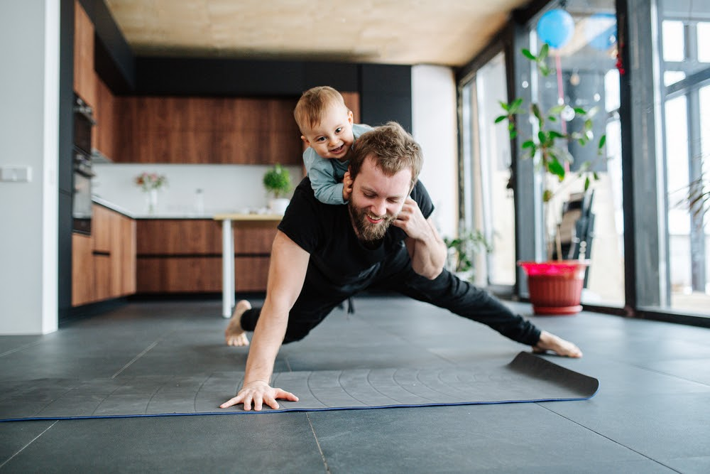 Man doing a one armed pushup with his son on his back