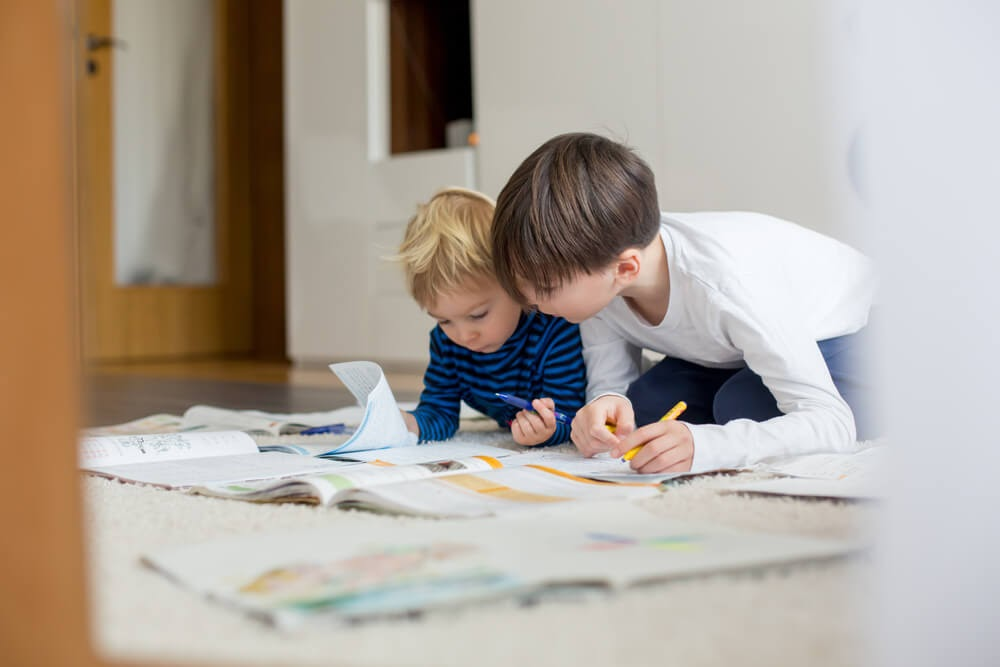 Two boys on the floor looking over some papers and books