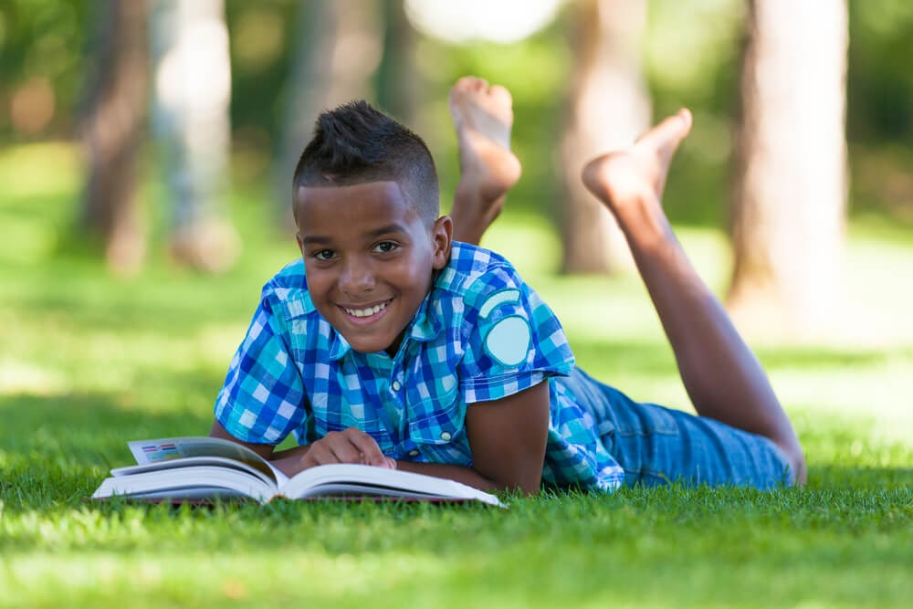 Boy reading in the grass with his feet up in tair