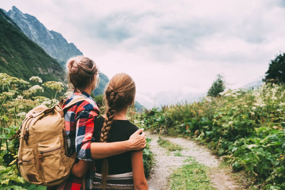 Woman and teenage daughter looking back at the scenery while on a hike