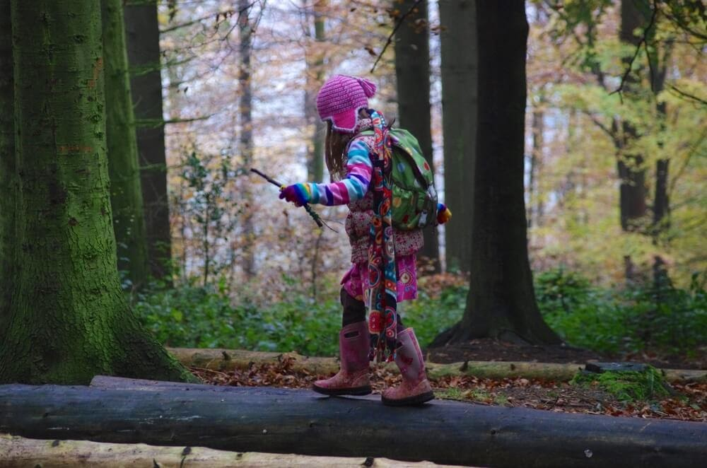 Girl balancing on a grounded tree in her rain gear and backpack