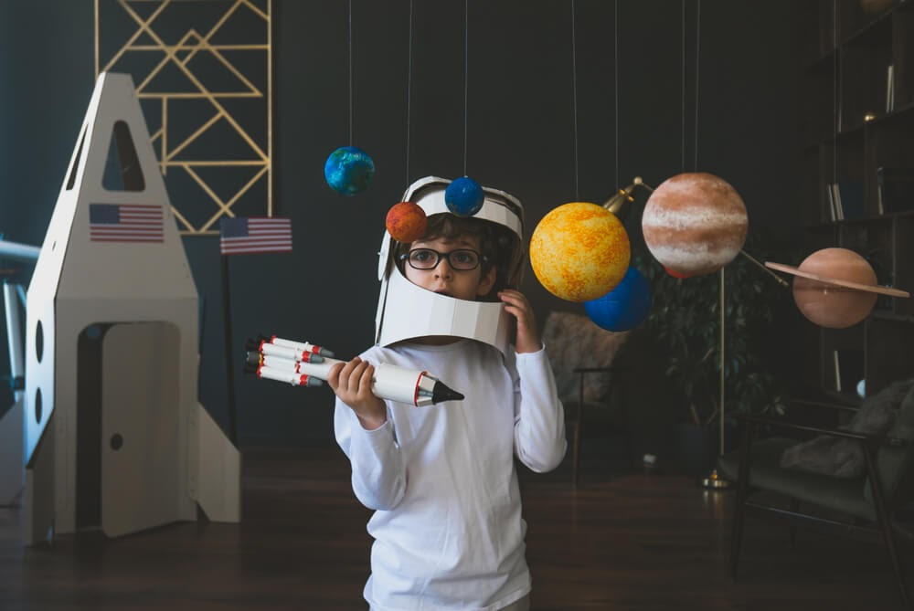Boy with cardboard astronaut gear and rocket playing space