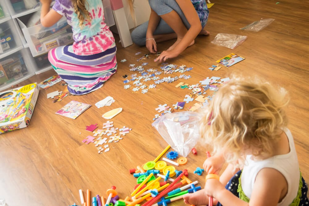 Sisters playing with puzzles and other learning toys on the floor