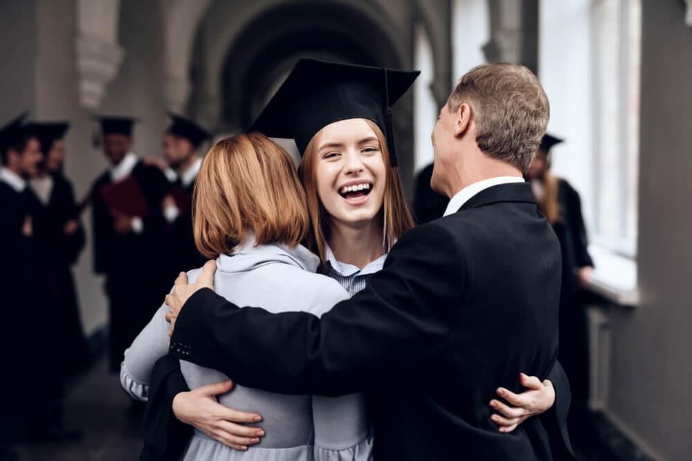 Girl in graduation gear hugging her parents