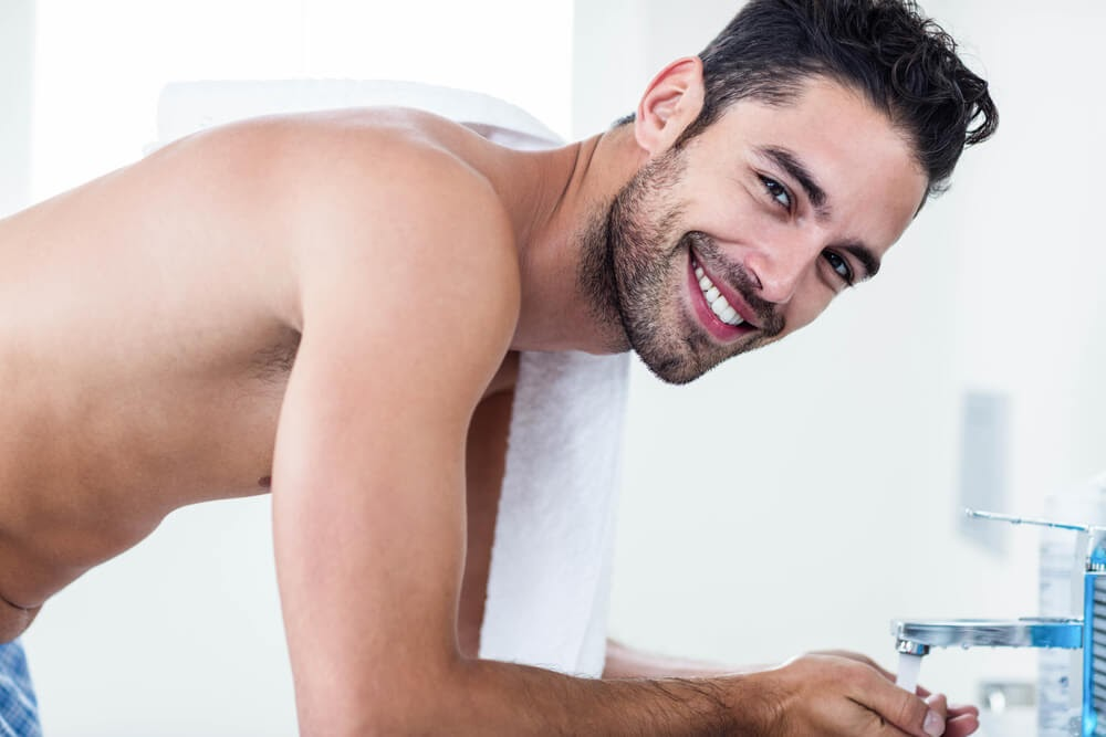Shirtless man smiling at the camera in his bathroom