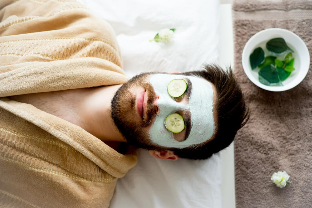 Man with a face mask with cucumbers on his eyes