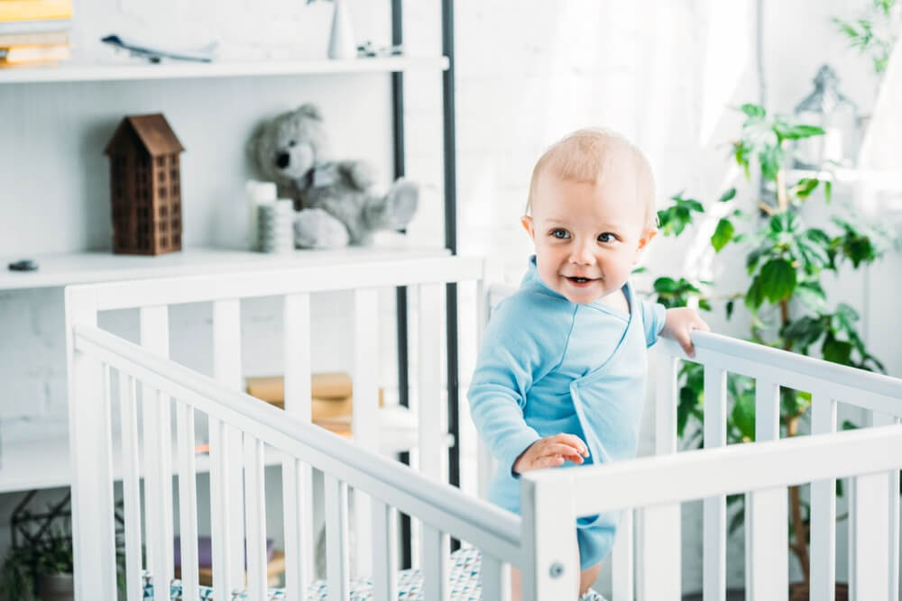Baby boy standing in his crib