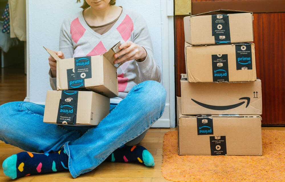Woman sitting on the ground opening an array of Amazon Prime boxes