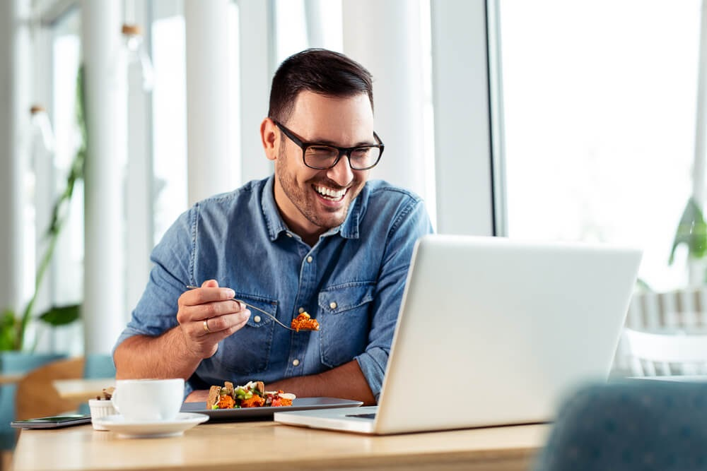 Man eating lunch and laughing with his computer