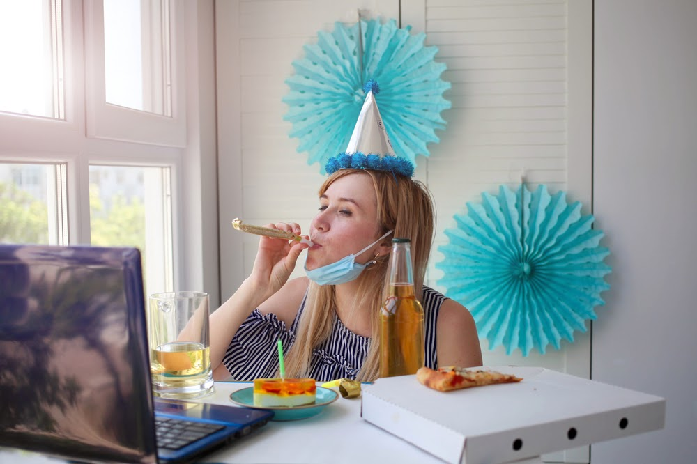 Woman drinking and blowing on a party favor in front of her computer