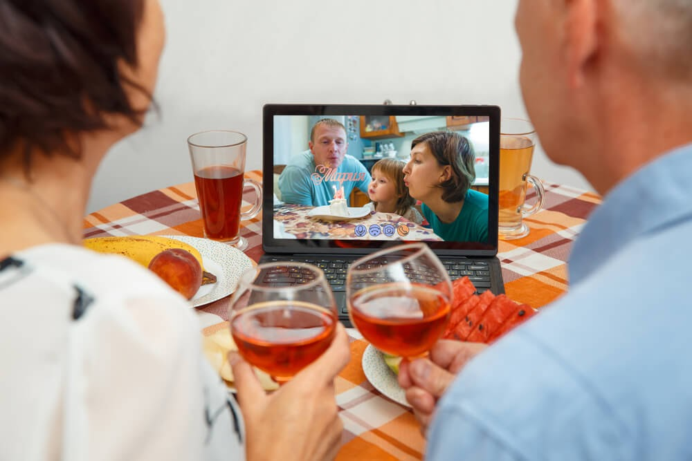 Two families enjoying a dinner party through Zoom