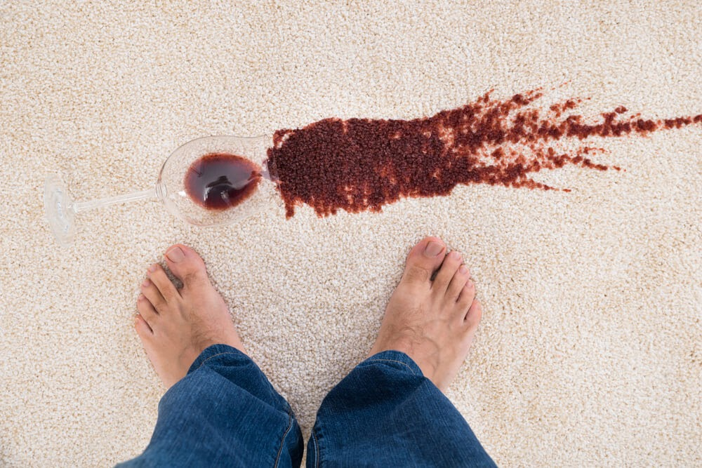 Glass of red wine, spilled on white carpet