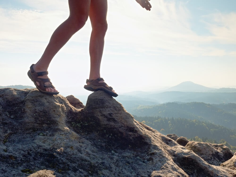 Close up of woman's feet as she stand on mountain cliff in her hiking sandals