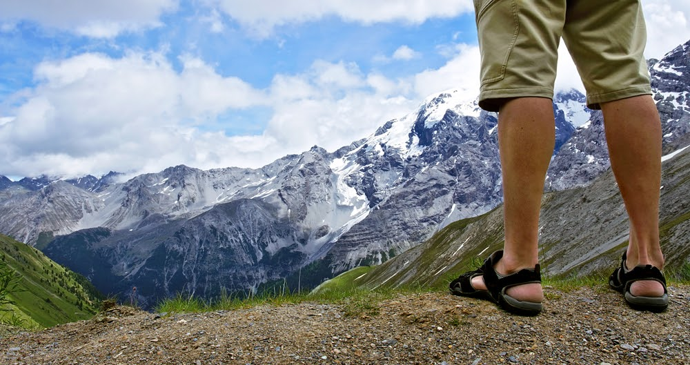 Man in hiking sandals overlooking some snowy mountains in the distance