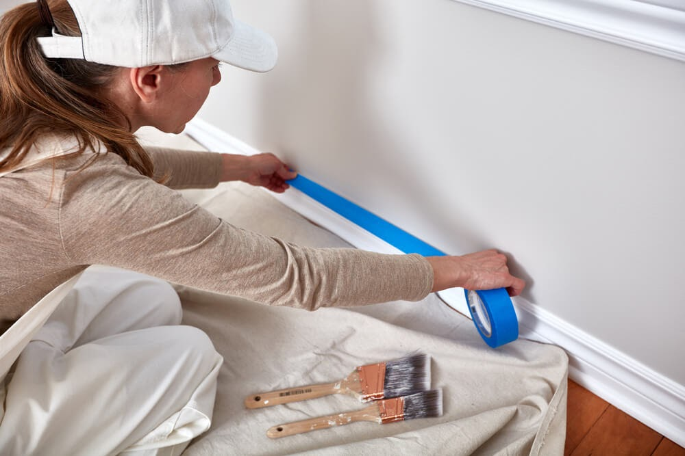 Woman taping off her wall trim