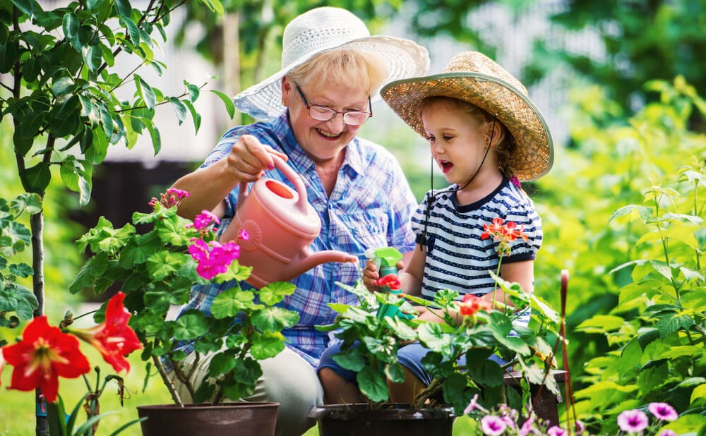 grandma and grand daughter watering plants with watering can