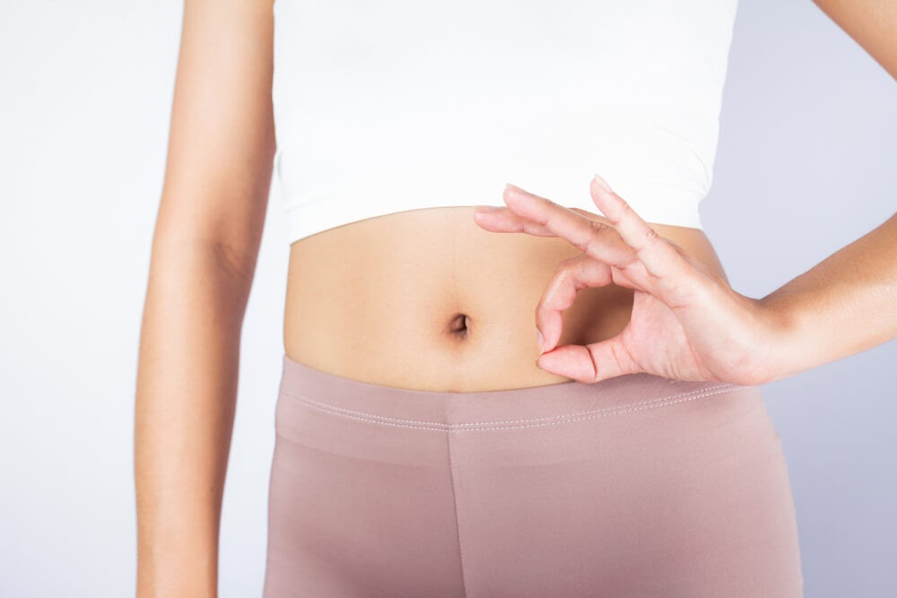 """Woman holding """"Ok"""" symbol with her hands over her belly"""