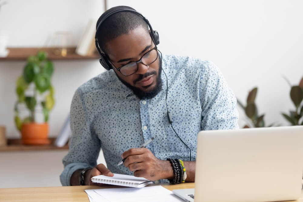 Man looking at his laptop with headphones on