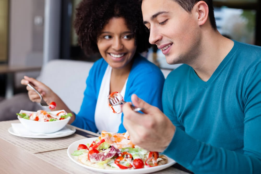 Young couple eating salads together