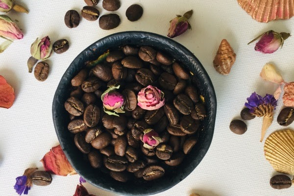 Flowers on top of a bowl of coffee beans