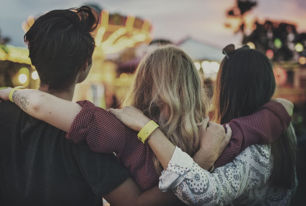 Friends with their arms around each other facing a carnival