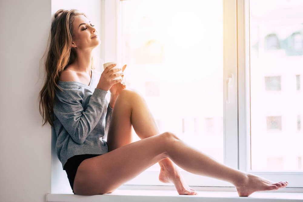 Woman enjoying her coffee next to a window in her panties